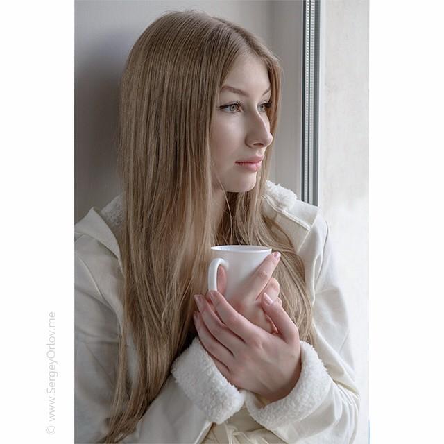 Красивая юная девушка в белом халате с белой чашкой в руке задумчиво смотрит в окно.