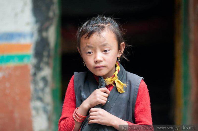 Замечательная непальская девочка, в волнении наблюдающая за играми сверстников. Детская школа, Ло, Верхний Мустанг, Непал