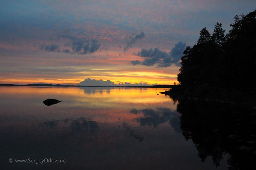 Потрясающе красивый облачный закат над озером в Карелии