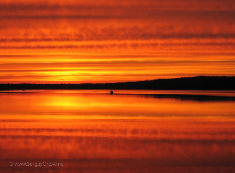 Потрясающий багровый закат в Карелии и удаляющаяся лодка на озере