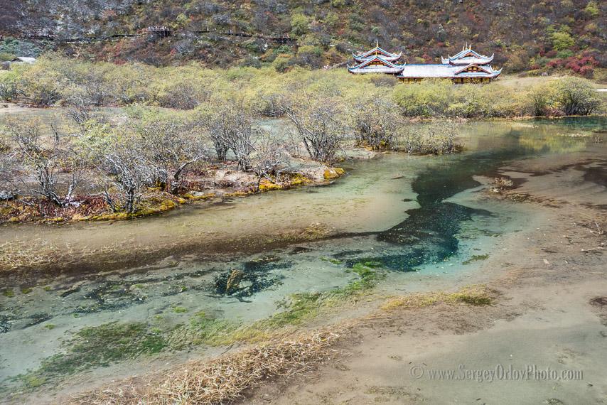 Древний буддистский храм и ручей с голубой водой, текущий по долине с разноцветными берегами. Заповедник Хуанлун, провинция Сычуань, Китай. Включен в список всемирного наследия ЮНЕСКО.