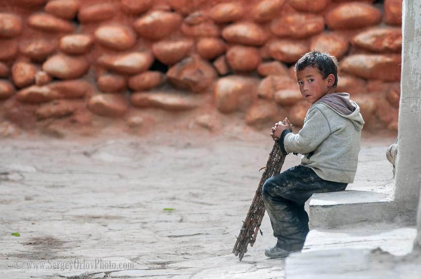 Маленький одинокий мальчик сидит в испачканной одежде на ступеньках дома в городе Ло Мантанг, Верхний Мустанг, Непал