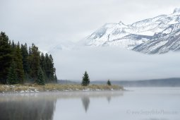 A distant mountain appeared through solid fog and clouds over a Maligne lake edge, Canada